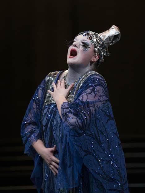 Foto di Rebeka Lokar mentre si esibisce come Turandot in uno splendido abito blu. Si vede solo lei dietro a uno sfondo nero