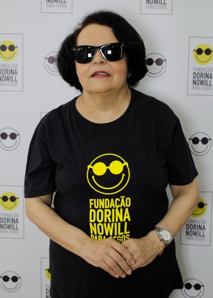 Foto di Regina che veste una t-shirt nera con uno smile giallo e occhiali da sole. Dietro a Regina c'è una parete con tanti smile in occhiali da sole simili a quello della sua maglietta