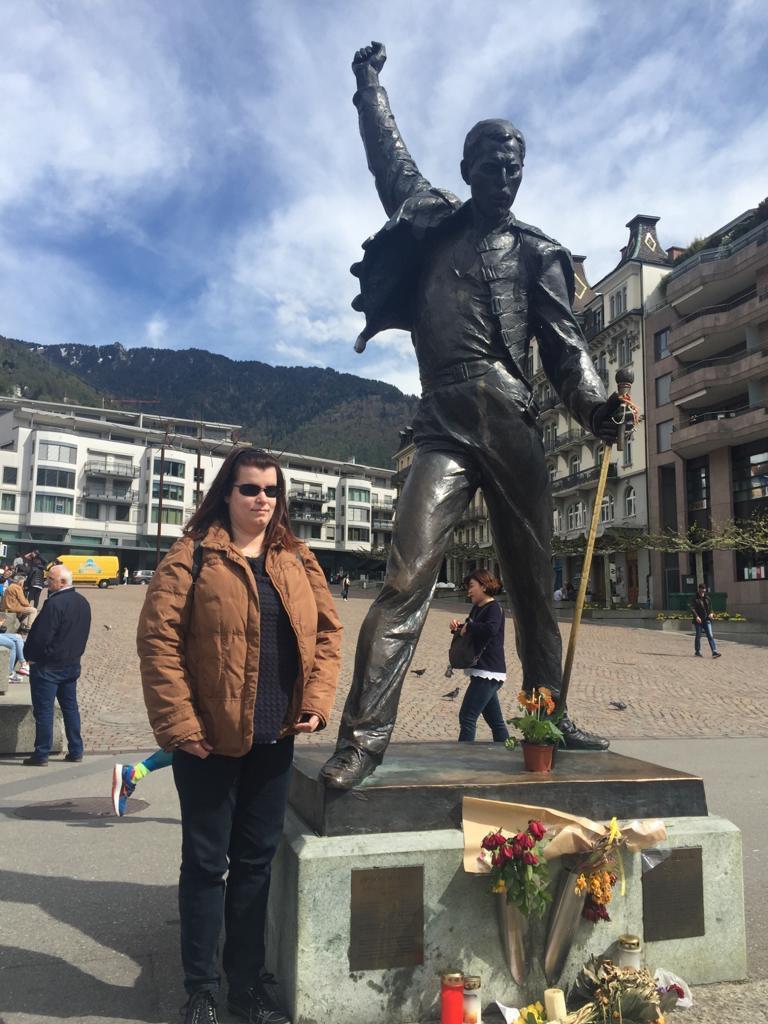 Elena posa sorridente a fianco alla statua di Freddie mercuri nella piazza di Montreux in Svizzera