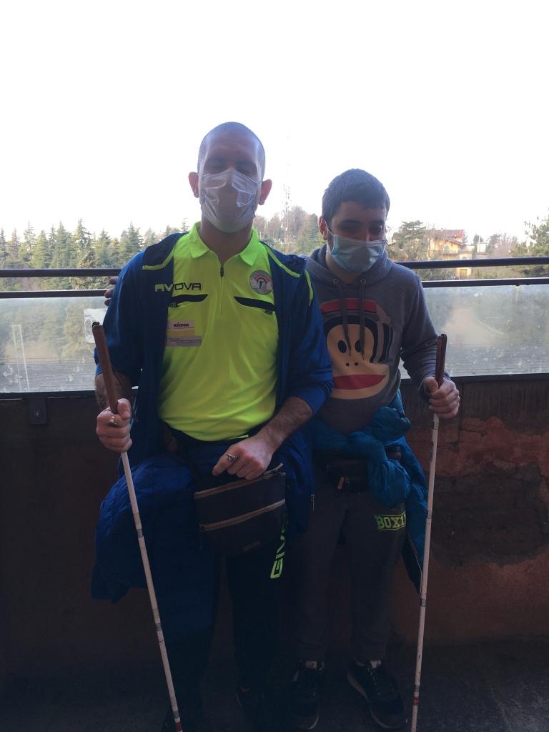 Foto di Roberto e Gabriele che posano con i loro bastoni bianchi dopo essere arrivati a piedi al parco della collina di San Luca a Bologna