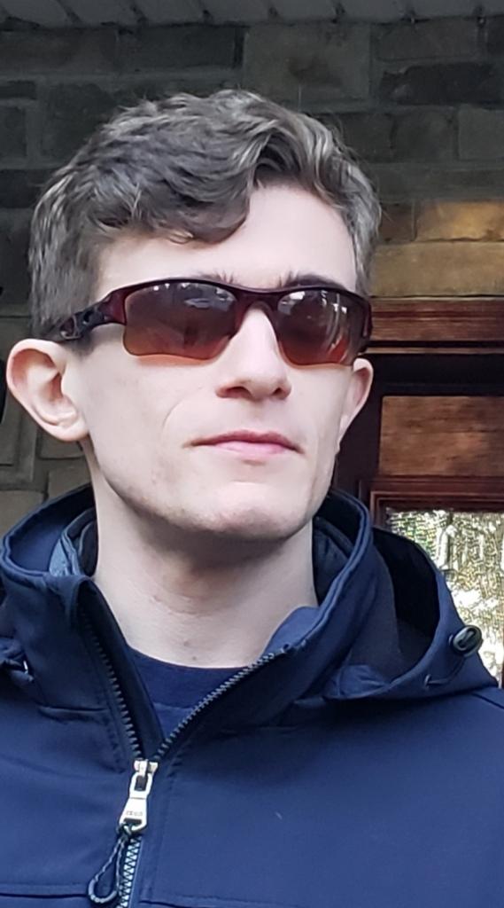 Primo piano di Albert in occhiali da sole e felpa blu. Dietro a lui una finestra