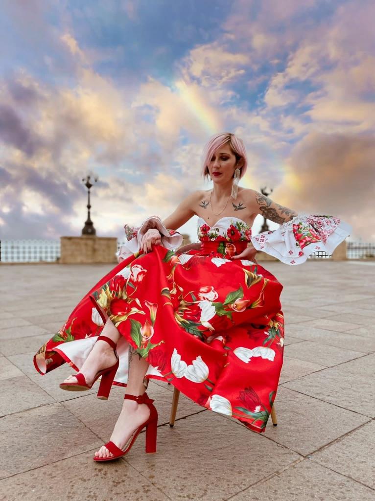 Foto di Alexandra che posa seduta su una piazza. Indossa un abito della sua collezione tutto rosso e composto da gonna e maglietta senza spalline. Ovunque è decorato con fiori bianchi e rossi e foglie. Alexandra ha i capelli rosa e sorride alla fotocamera.