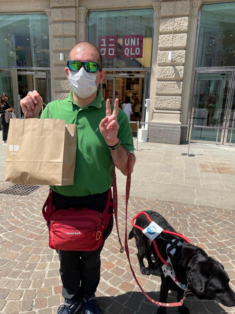 Foto di Roberto davanti all'ingresso di Uniqlo a Milano. Sfoggia una borsa i carta beige con la scritta Uniqlo