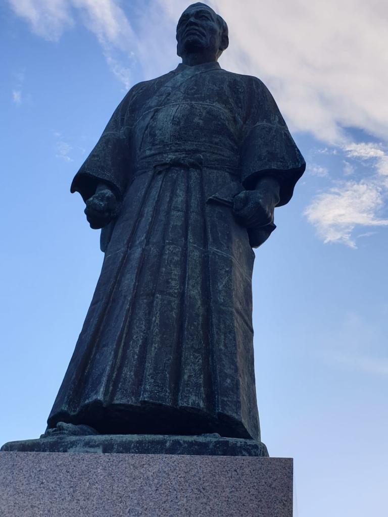 Foto della statua in bronzo di John Manjiro. Veste un kimono da uomo e nelle mani stringe uno strumento per la navigazione simile ad una squadra