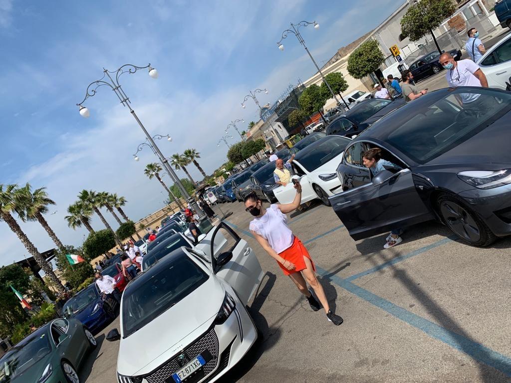 Cinzia passeggia tra una moltitudine di macchine elettriche alla manifestazione di Taranto