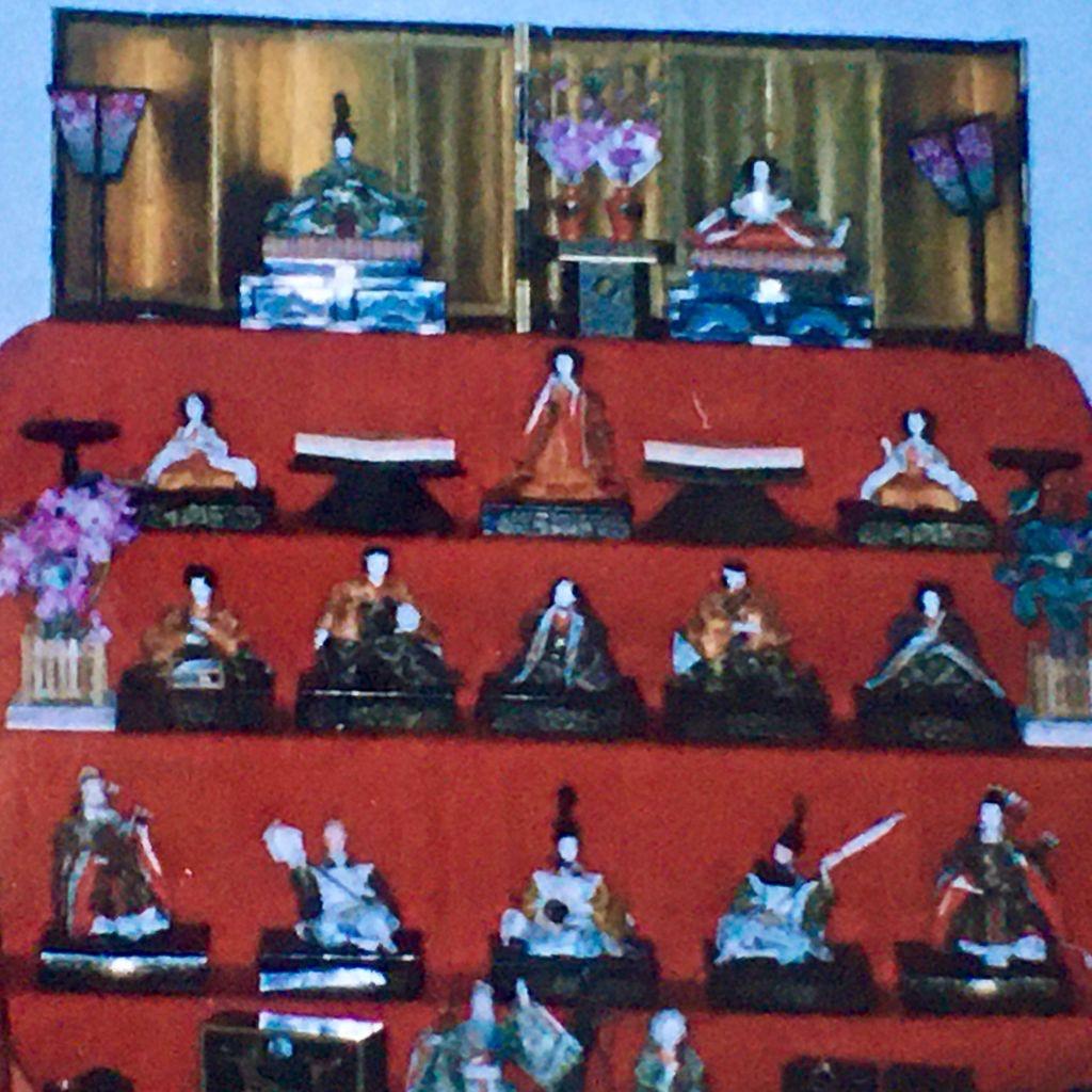 Nella foto, una piattaforma a scala su cui è adagiato un telo rosso. Su ogni gradino sono poste le bambole giapponesi dello Hina Matsuri, la festa delle bambole. La rappresentazione simboleggia un matrimonio di alta casta del periodo Heian