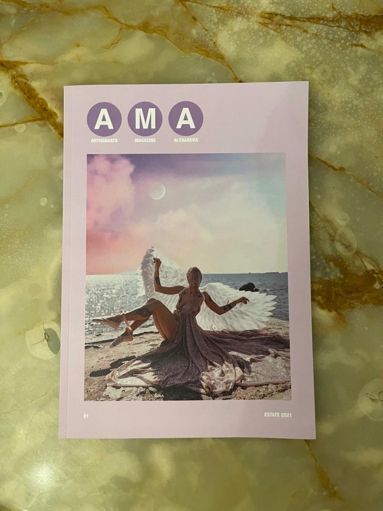 Copertina di AMA tutta rosa. Nel centro, la foto di Alexandra vestita come un angelo, sorride alla fotocamera seduta su una scogliera