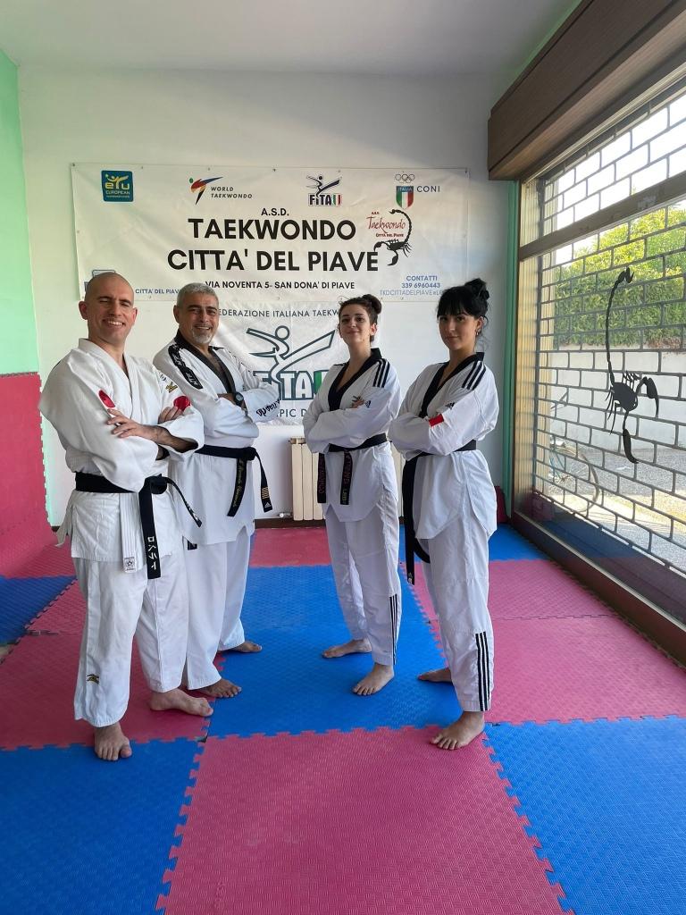 Gruppo in posa a forma di lettera Vu. In piedi sul tatami. Tutti indossano il Dobok a parte Roberto in judogi. Da sinistra, Roberto, Maestro Chiumento, Isabella e Michelle. Sul fondo, l'insegna del Taekwondo Città del Piave.