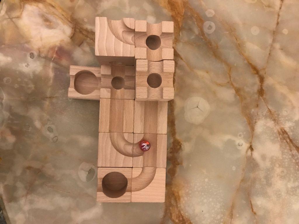 Foto del gioco Kuboro. Alcuni cuvi di legno sono affiancati e sulla faccia superiore formano una pista per le biglie