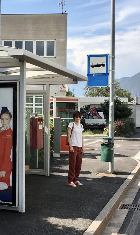 Una ragazza con una maglietta bianca e uno zaino è ferma ad una fermata del bus. Si vede la tettoia trasparente e il palo con il cartello identificativo, su sfondo bianco un autobus nero.