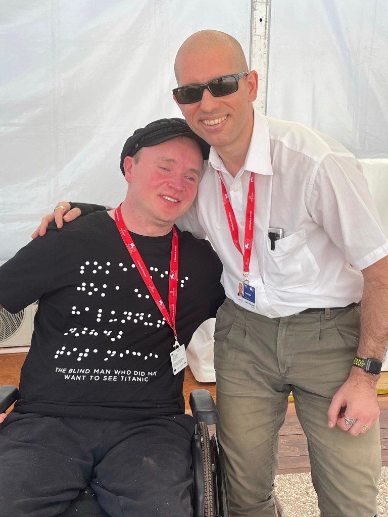 Mister Poikolainen in sedia a rotelle posa assieme a Roberto presso l'hoolywood lounge del lido di venezia. Indossa una maglietta in braille del suo film