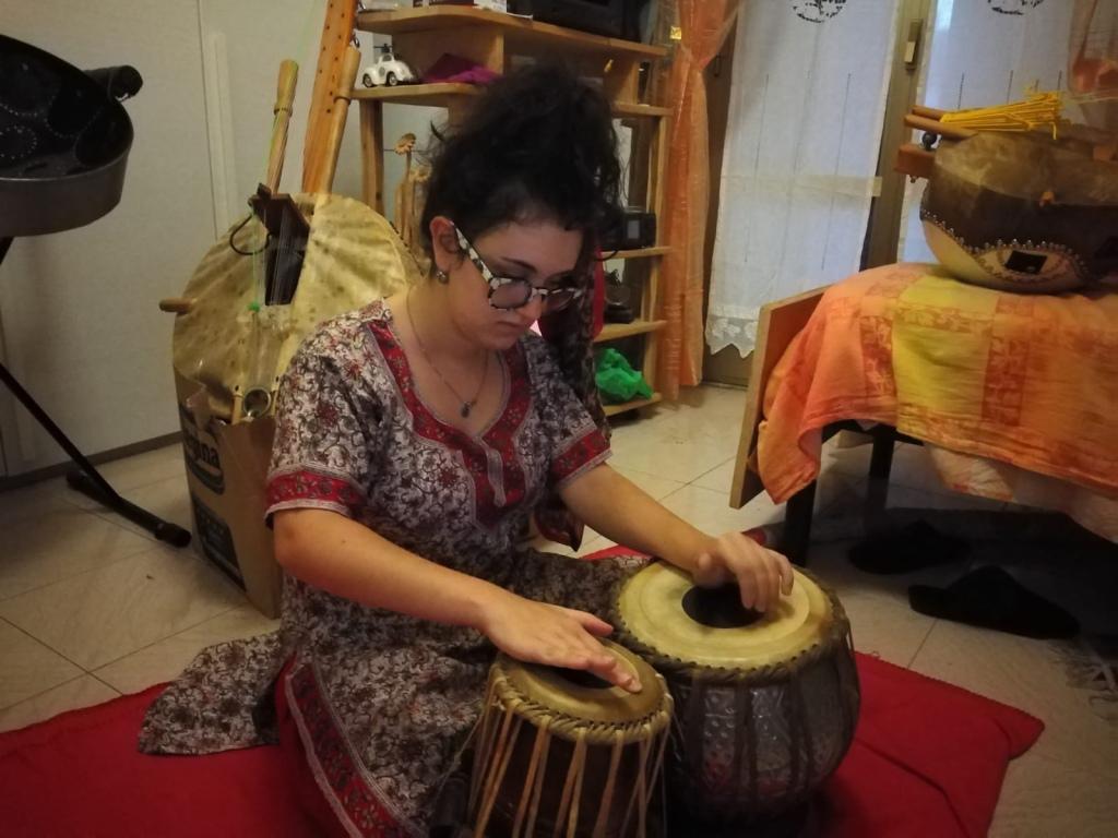 Clarissa suona le tabla indossando un vestito di seta indiano