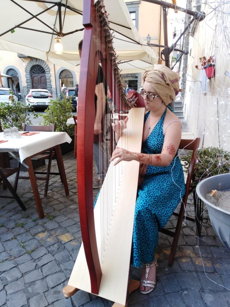 Clarissa suona l'arpa. Indossa un vestito di seta celeste e un turbante dorato