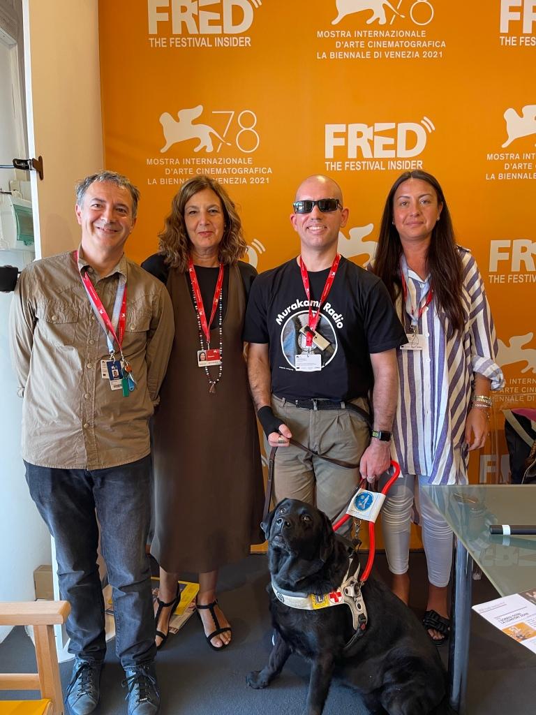 Foto di gruppo a FRED Radio. Sfondo arancione e davanti a tutti Atena, il cane guida di Roberto che guarda verso l'obiettivo